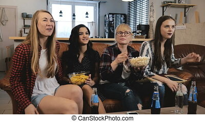 Female friends watch TV show with snacks at home. Young...