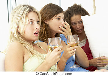 Female Friends Watching A Scary Movie Together