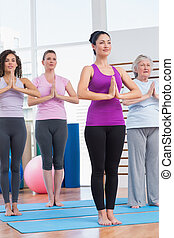 Female friends with hands clasped exercising in gym - Full...