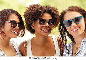 happy young women in sunglasses outdoors