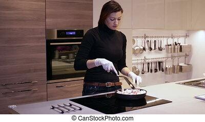 Female fry meat in a frying pan