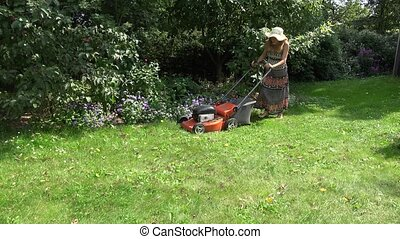 Female garden worker cutting lawn near flower beds and fruit trees. 4K