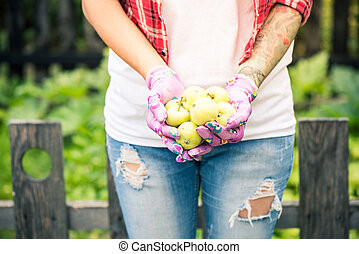 Female gardener holding green apples in hands