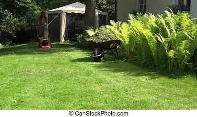 female gardener in shorts and bra pushing lawn grass mower near fern.