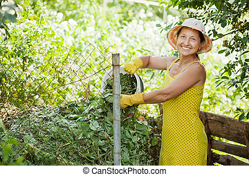 gardener making compost - Female gardener making compost in...