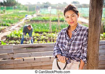 Female gardener posing with a shovel in garden