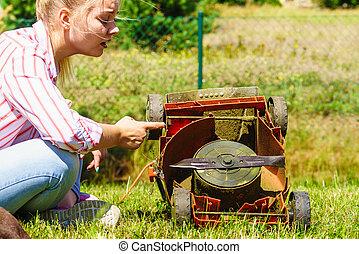 Female gardener with broken lawnmower
