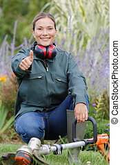female gardener with earmuffs showing okay sign