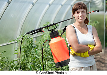 Female gardener  with knapsack garden spray