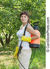 Female gardener working  with  garden spray