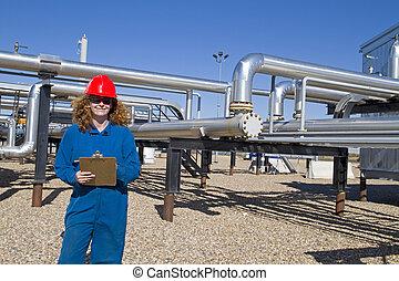 Female gas field operator inspects compressor site