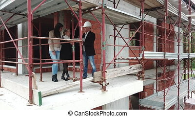 Female Gay Couple Buying New Home In Construction Site -...