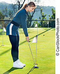 Female golf player getting ready to hit ball