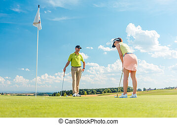 Female golf player ready to hit the ball