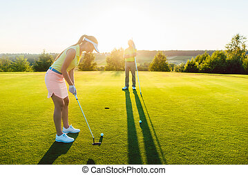 Female golf player ready to hit the ball into the cup