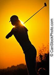 Female golfer at sunrise