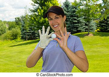 Female golfer holding a golf ball