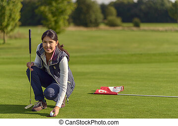 Female golfer pickung up a golf ball