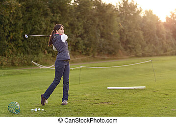 Female golfer practicing on a driving range