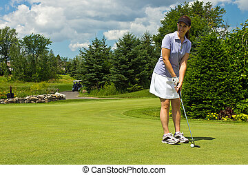 Female golfer putting the golf ball on the green