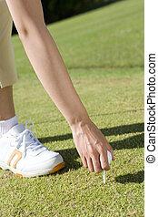 female golfer setting up a tee