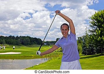 Female golfer stretching with a golf club
