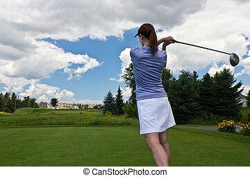 Female golfer swinging her golf club