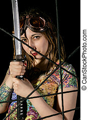 Female gothic warrior in pilot old glasses posing with katana sword