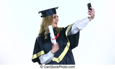 Female graduate makes selfie photo with diploma. White. Slow...