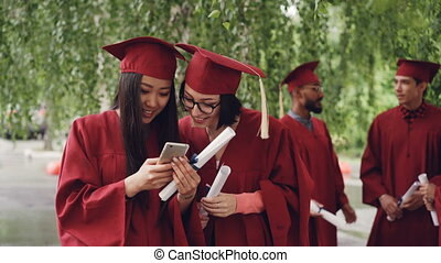Female graduates are using smartphone looking at screen talking and laughing standing outdoors holding diplomas, girls are wearing formal gowns and hats.