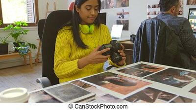 Female graphic designer looking at photographs 4k