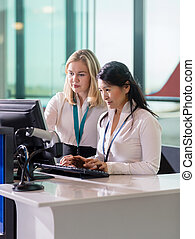 Female Ground Staff Using Computer At Reception In Airport