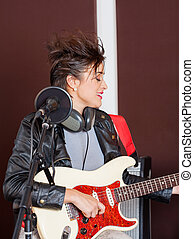 Female Guitarist Performing In Studio