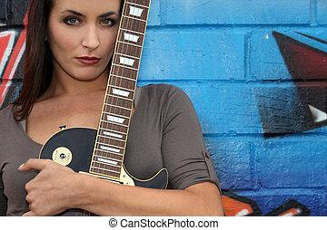 Female guitarist standing in front of graffiti