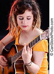 Female guitarist with dreadlocks playing guitar
