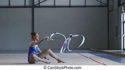 Side view of focused teenage Caucasian female gymnast performing at the gym, exercising with ribbon, spinning the ribbon, sitting on the floor, wearing blue leotard in slow motion.