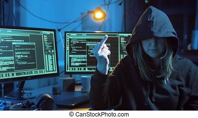female hacker showing middle finger in dark room -...