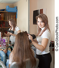 Female hair stylist working with girl