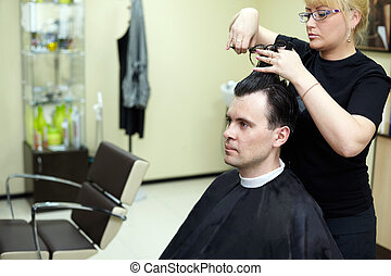 Female hairdresser cuts  man hair in the hairdressing salon