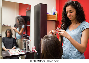 Female hairdresser cutting hair with scissors
