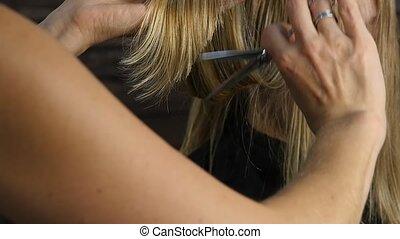 Female hairdresser do haircut closeup. Hair clipper....