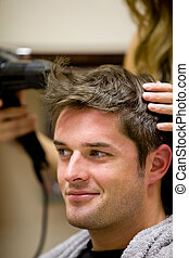 Female hairdresser drying her male customer\'s hair in her...