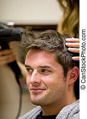 Female hairdresser drying her male customer\'s hair in her...