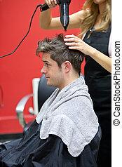Female hairdresser drying her male customer's hair in her...