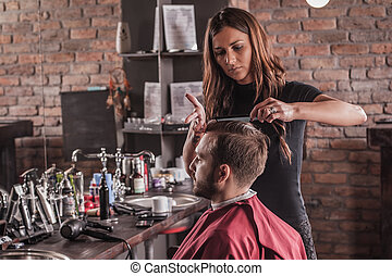 Female hairdresser hairstyle hair of man in chair