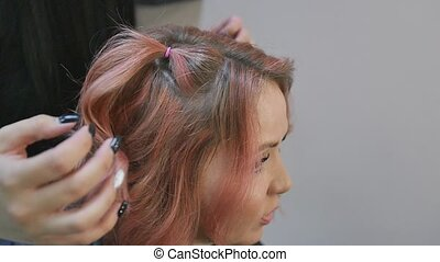 Female hairdresser makes hairstyle for a red-haired ...