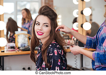 Female hairdresser making hairstyle to cute woman in beauty...