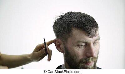 Female hairdresser shaping mens hair cutting uses scissors...
