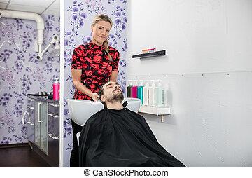 Female Hairdresser Washing Customer's Hair In Salon