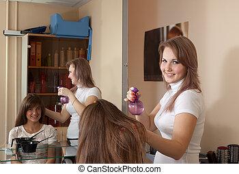 Female hairdresser working with spray